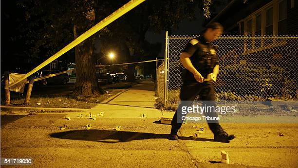 A police evidence technician places markers on bullet casings at the scene of a double shooting on the 8700 block of South Sangamon Street Saturday...