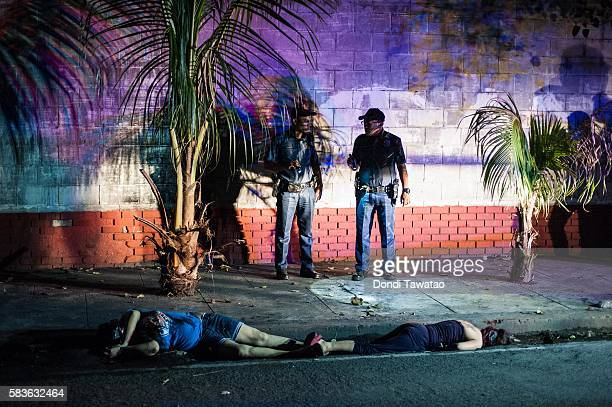 Police examine the bodies of two female victims of a summary execution with their mouth and eyes wrapped in tape on July 21 2016 in Manila...