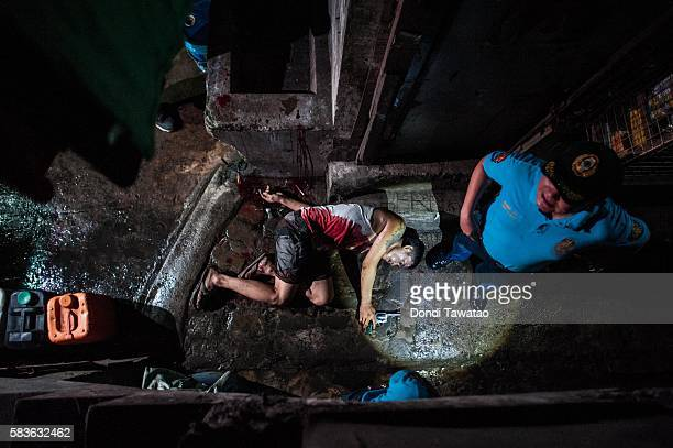 Police examine the body of an alleged drug dealer killed in a shooutout with swat teams during a drug raid on July 21 2016 in Manila Philippines...