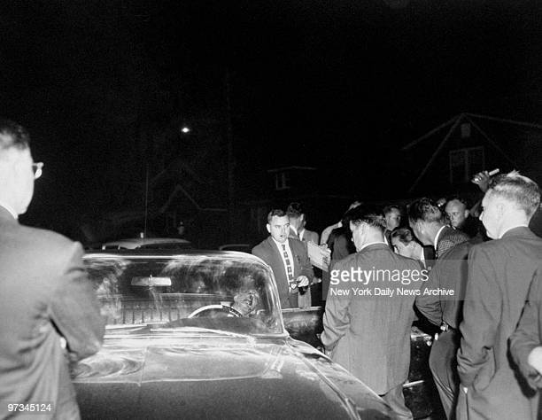 Police examine the car in which lies Little Augie Pisano after he was found slain in his Cadillac along with Janice Drake