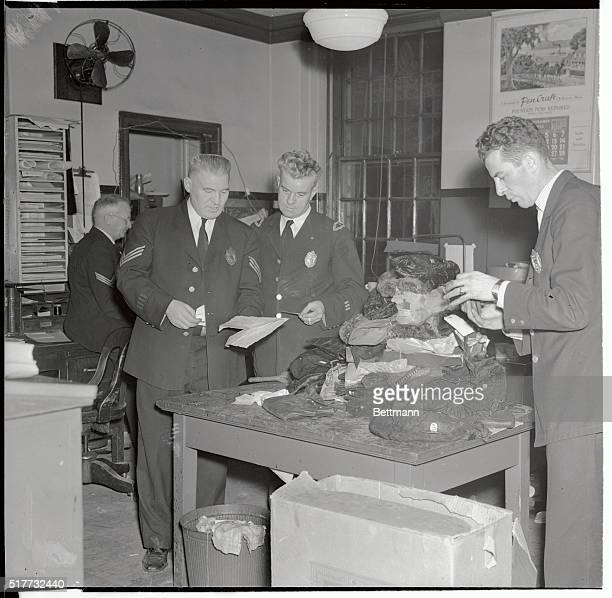 Police examine the pocketbooks of women victims of the Boston fire in an effort to establish the identity of the owners But most women who perished...
