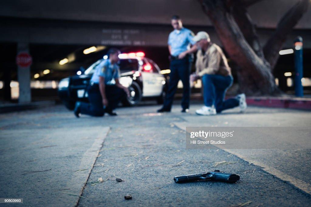 Police examining crime scene with gun on ground : Stock Photo