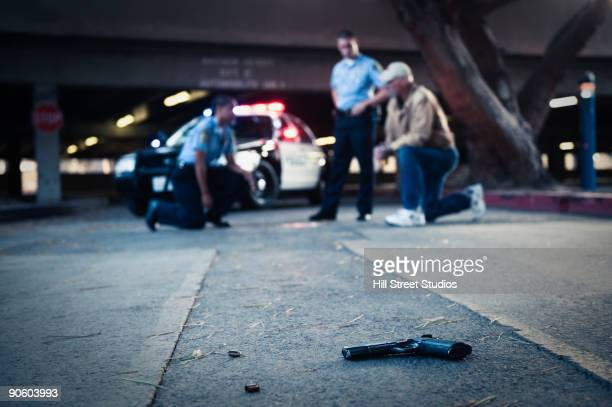 police examining crime scene with gun on ground - justiça criminal - fotografias e filmes do acervo