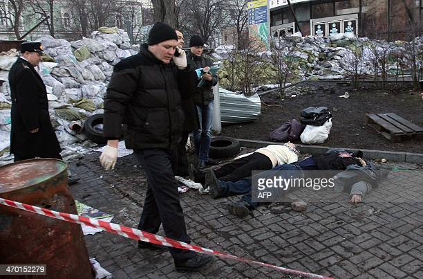 Police experts examine bodies of the dead antigovernment protesters after their clashes with the police in Kiev on February 18 2014Ukrainian riot...