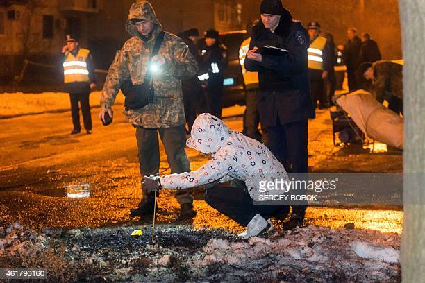 Police experts examine the place of a blast near the district court in northeastern Ukrainian city of Kharkiv on January 19 2015 Thirteen people were...