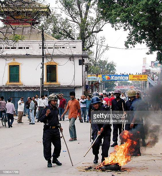 Police extinguish a burning tire set alight by demonstrators who were against the crowning of the new King Gayanendra 04 June 2001 in Kathmandu One...