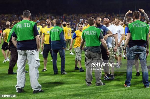Police face Braunschweig fans after the Bundesliga Playoff leg 2 match between Eintracht Braunschweig and VfL Wolfsburg at Eintracht Stadion on May...