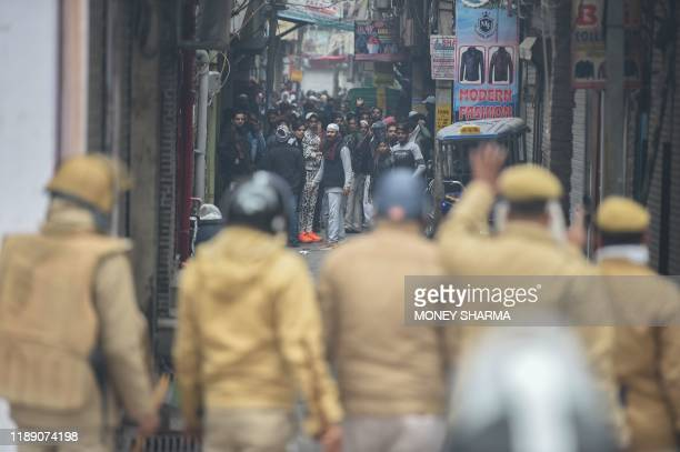 Police face men standing in a narrow street as protesters gathered to demonstrate against India's new citizenship law in New Delhi on December 17,...