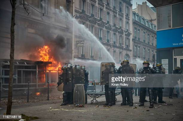 Police face towards protestors as demonstrations turn violent during a rally near Place de Republique in support of the national strike in France one...