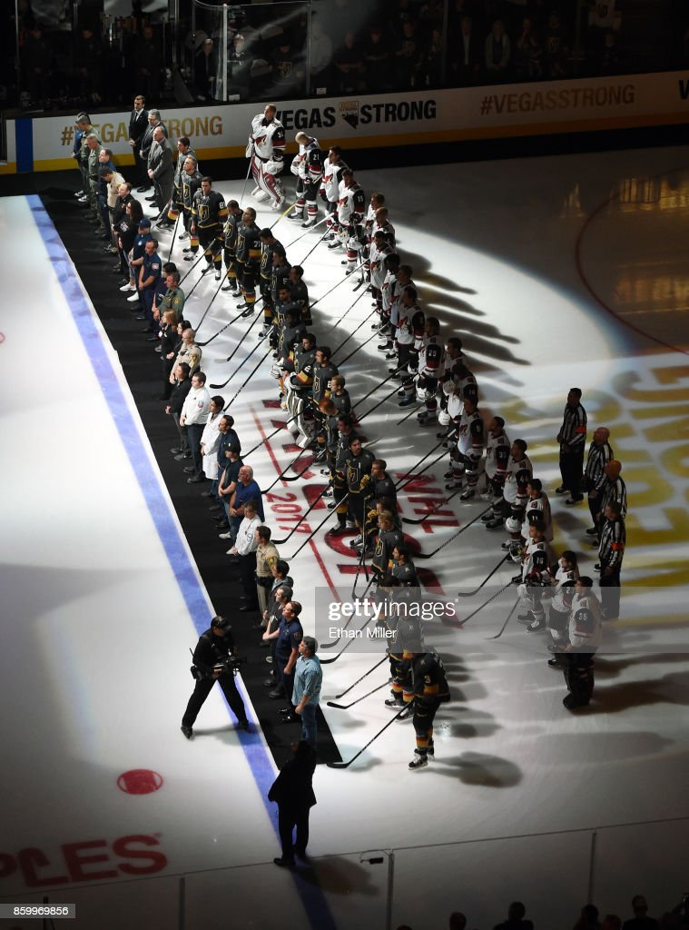 Police, fire and medical personnel (L) line up on the ice in front of the Vegas Golden Knights (C) and the Arizona Coyotes (R) before the Golden Knights' inaugural regular-season home opener against the Coyotes at T-Mobile Arena on October 10, 2017 in Las Vegas, Nevada. The Golden Knights honored first responders and victims of last week's mass shooting at the game. On October 1, Stephen Paddock killed 58 people and injured more than 450 after he opened fire on a large crowd at the Route 91 Harvest country music festival. The massacre is one of the deadliest mass shooting events in U.S. history.