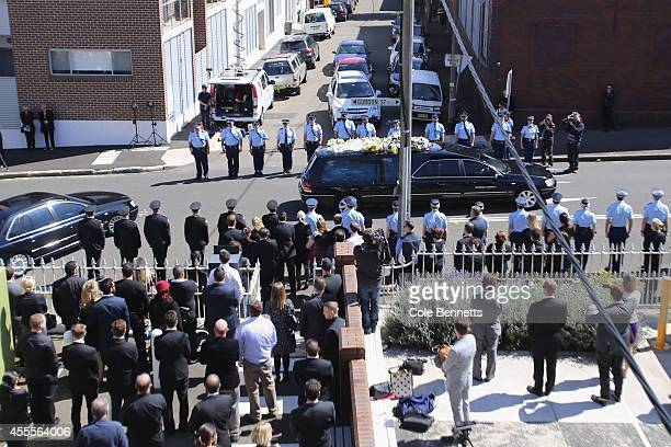 Police fire brigade friends and family provide a guard of honor as the hearse moves on to the cemetary at a service to remember Bianka O'Brien and...