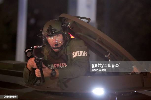 Police fire pepper balls from an armored vehicle as they confront demonstrators outside of the Kenosha County Courthouse during a third night of...