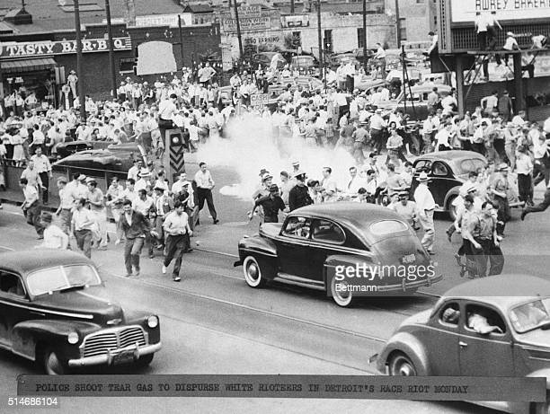 Police fire tear gas during a race riot in Detroit where a curfew has been imposed and a state of emergency declared White rioters are seen fleeing...