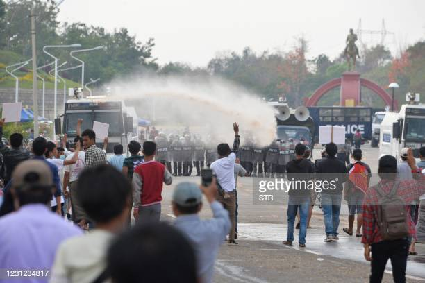 Police fire water cannon on protesters during a demonstration against the military coup in Naypyidaw on February 18, 2021.