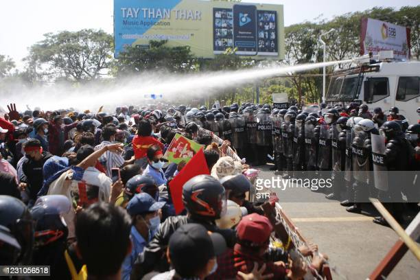 Police fire water cannons at protesters as they continue to demonstrate against the February 1 military coup in the capital Naypyidaw on February 9,...