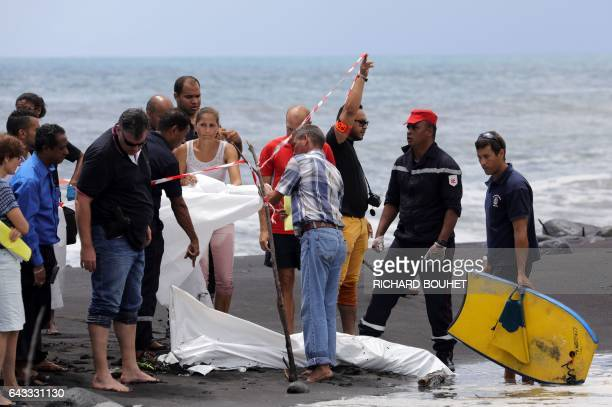 Police firefighters and people stand next to the body of a bodyboarder killed by a shark covered by a white cloth on February 21 2017 on a beach in...