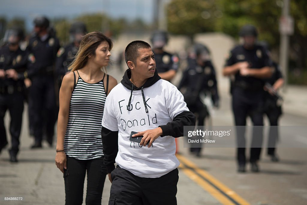 Police force protesters down a street, away from Donald Trump supporters jeering from a parking structure, near a campaign rally by presumptive GOP presidential candidate at the Anaheim Convention Center on May 25, 2016 in Anaheim, California. Previous visits by the candidate to Orange County have sparked in protests that resulted in some arrests. The presidential candidates are campaigning in Southern California for the June 7 California primary.