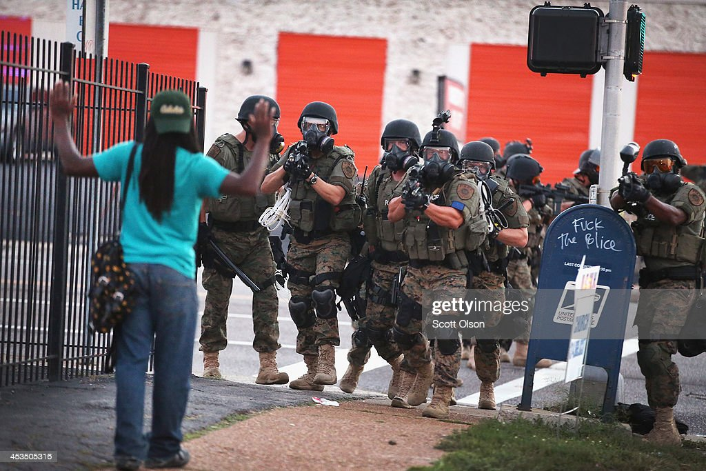 Police force protestors from the business district into nearby neighborhoods on August 11, 2014 in Ferguson, Missouri. Police responded with tear gas and rubber bullets as residents and their supporters protested the shooting by police of an unarmed black teenager named Michael Brown who was killed Saturday in this suburban St. Louis community. Yesterday 32 arrests were made after protests turned into rioting and looting in Ferguson.