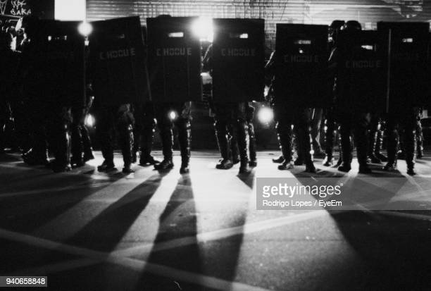 police force standing with riot shield on illuminated street - social justice concept stock pictures, royalty-free photos & images