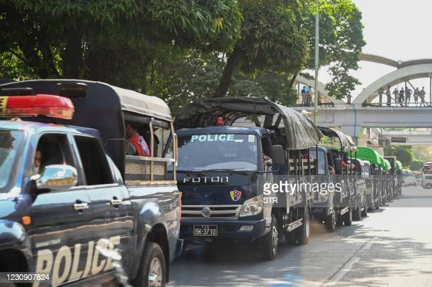 Police forces are pictured in a line of trucks in the downtown area of Yangon on February 1 as Myanmar's military detained the country's de facto...