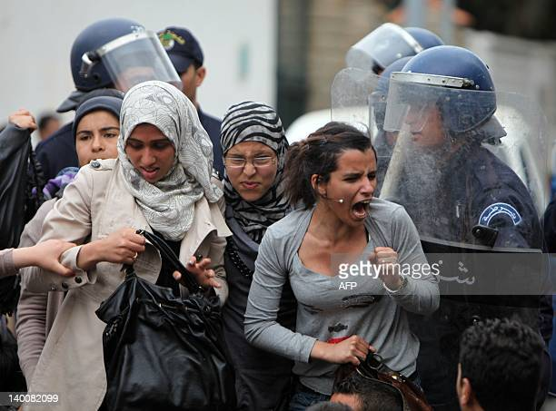 Police forces clash with women students who tried to stage a protest against the government in front of the presidential palace in Algiers on April...
