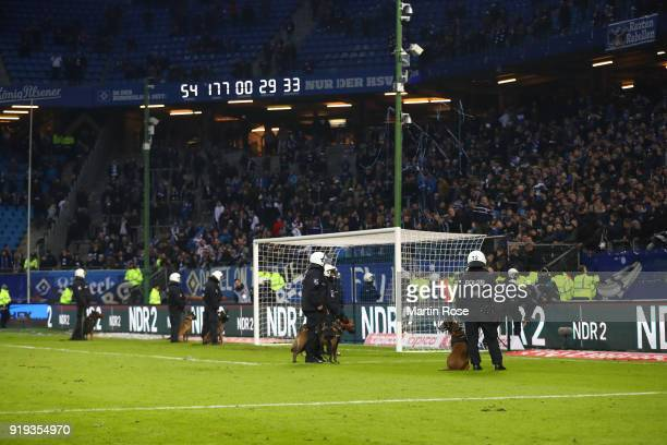 Police forces enter the pitch with dogs in front of the Hamburg stand after the Bundesliga match between Hamburger SV and Bayer 04 Leverkusen at...