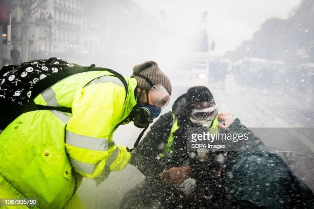 Police forces fire water cannon at Yellow Vest protesters near the Arc De Triomphe during a 'Yellow Vest' protest in Paris Without any political...
