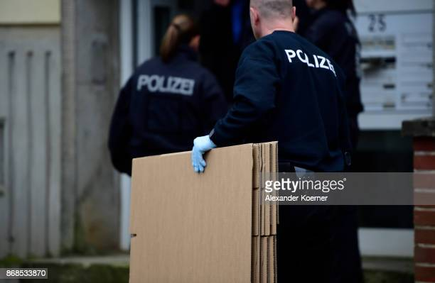 Police forces of the German Federal Police carry boxes into the apartment police raided hours before and where they arrested a Syrian man on October...