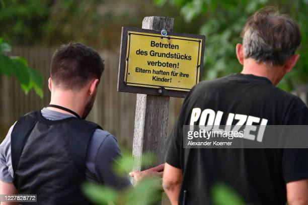 Police forces re-erect a sign of private property at the allotment, which the police searched for two days in relation to the disappearance of...