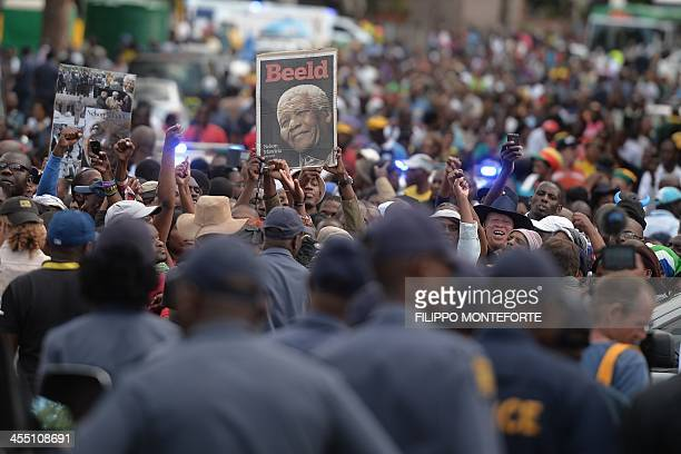 Police forces stand guard as a crowd of people waits outside the Union Buildings in Pretoria to bid farewell to South African former president Nelson...