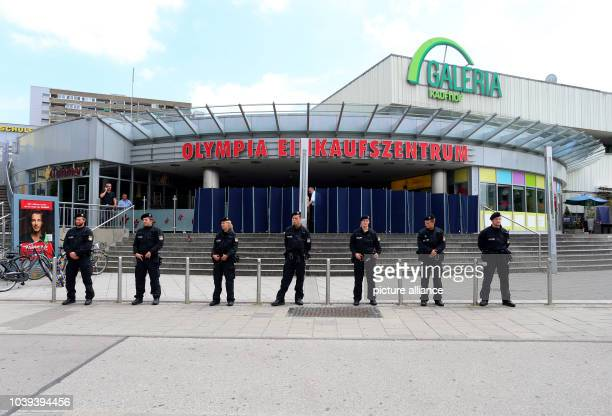 Police forces stand in front of the Olympia Einkaufszentrum one day after a shooting with deaths and casualties in the building in MunichGermany 23...