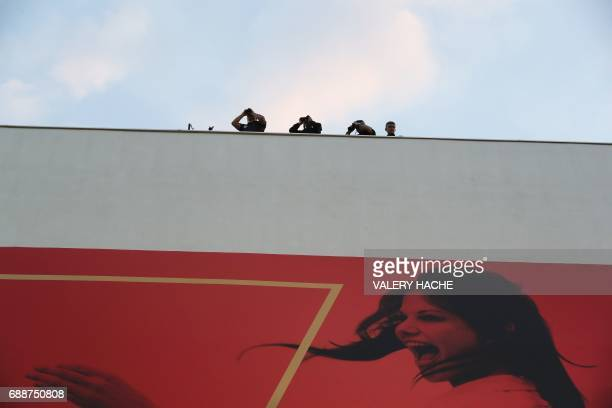 Police forces use binoculars for surveillance from the rooftop of the Festival's Palace as the film cast leaves on May 26 2017 following the...