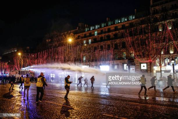 Police forces use water canons to disperse demonstrators of the French 'yellow vests' movement from the Champs Elysees avenue at the end of a protest...