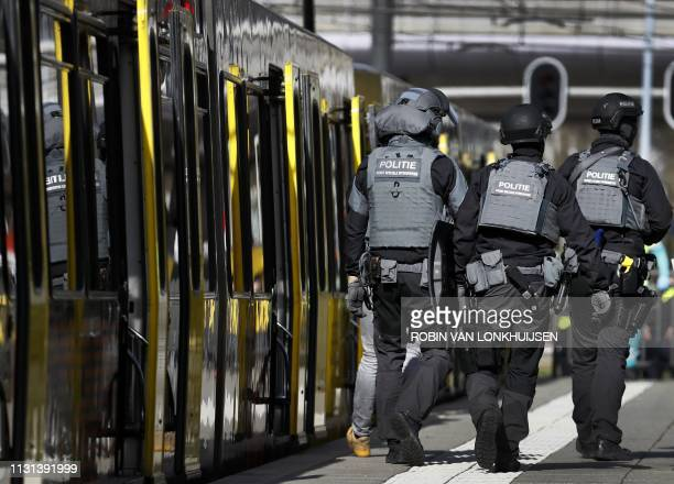 Police forces walk near a tram at the 24 Oktoberplace in Utrecht, on March 18, 2019 where a shooting took place. - A gunman who opened fire on a tram...