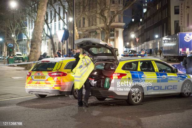 Police forensic crime scene teams arrive on the cordon line of the scene where a man has been shot dead by police in whitehall overnight on March 9,...