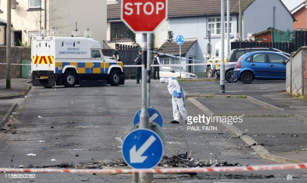 A police forensic expert inspects the scene where a journalist was fatally shot amid rioting overnight in the Creggan area of Derry in Northern...
