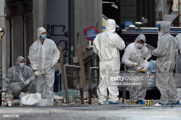 Police forensic experts search for evidence outside the Greece's industry association offices in Athens after a bomb exploded early on November 24...