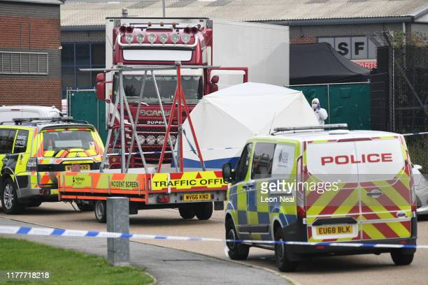 Police forensic investigation officers stand in front of the site where 39 bodies were discovered in the back of a lorry on October 23, 2019 in...