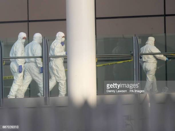 Police forensic investigators walk along a bridge linking Victoria Station with the Manchester Arena where a suspected terrorist attack at the end of...