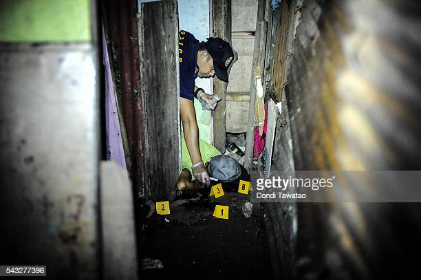 A police forensic officer inspects a body after a shootout which killed 3 suspected drug dealers during a buy bust operation on June 25 2016 in...