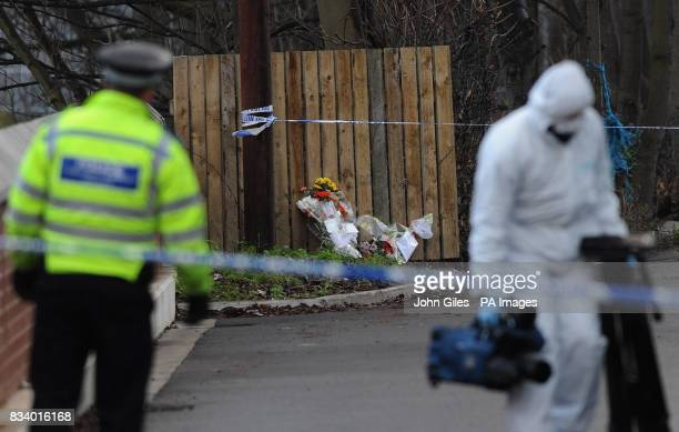 A Police forensic officer looks at floral tributes at the house in Wakefield where ArchieLee Hirst was killed by a dog