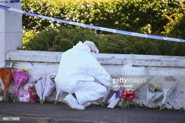 A police forensic officer looks at flowers outside a house on Ardbeg Road following the discovery of the body of six year old Alesha MacPhail on July...