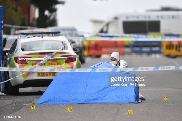 Police forensic officer looks under a small blue police tent covering an area of road in Irving Street in Birmingham after a number of people were...