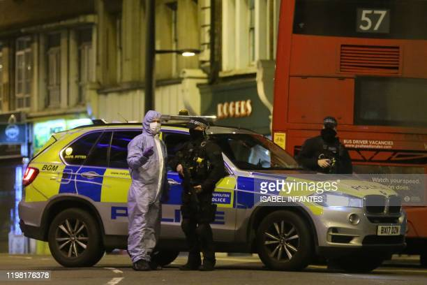 A police forensic officer speaks with a police officer as he works on Streatham High Road in south London on February 2 after a man is shot dead by...