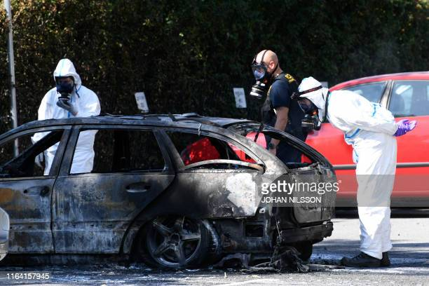 Police forensic officers inspect a burnedßout car near the scene where a woman was shot dead in the Ribersborg district of Malmo Sweden on August 26...