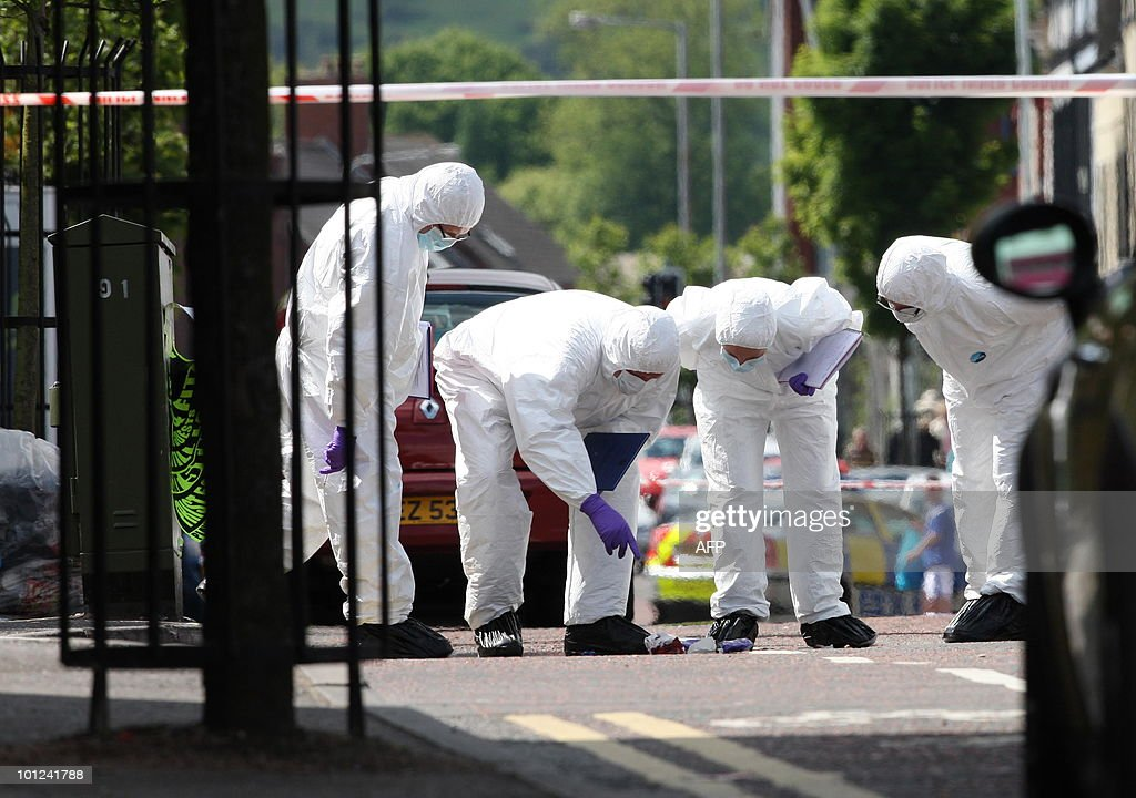 Police forensic officers inspect an area were a man was shot on the Shankill Road in Belfast, Northern Ireland, on May 28, 2010. A man was shot dead Friday on the Shankill Road in Belfast, a staunchly Protestant area of Northern Ireland's capital, police said. The victim was crossing the street, a notorious hotspot during the British province's three decades of sectarian violence, when he was felled by a burst of gunfire, a police source told.