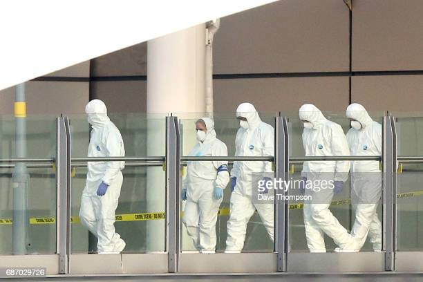 Police forensic officers leave the Manchester Arena as they investigate the scene of an explosion on May 23, 2017 in Manchester, England. An...