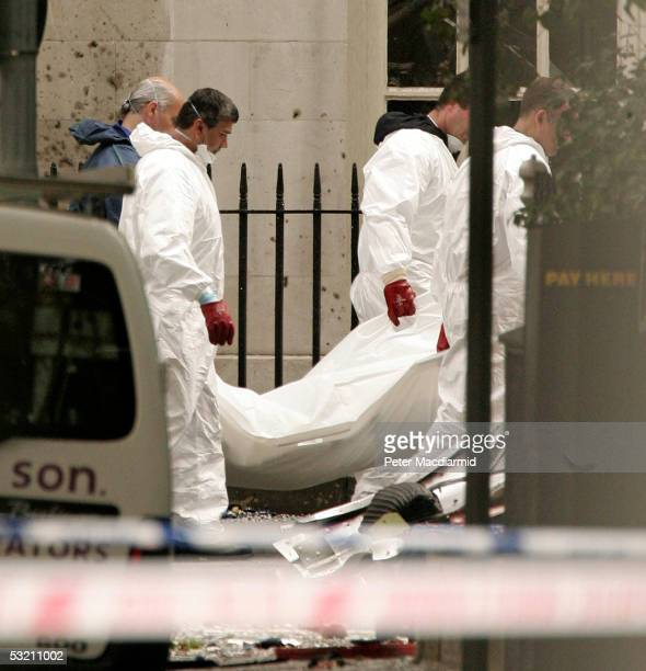Police forensic officers remove a body from the scene of a bus bombing on July 8 2005 in London At least 50 people were killed and 700 injured during...