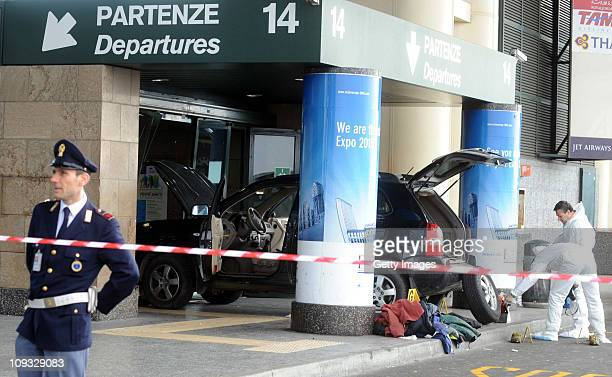 Police forensic officers stand by a car that crashed into in the departure terminal of Malpensa Airport on February 21 2011 in Milan Italy A Tunisian...