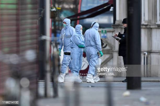 Police forensic officers work on Streatham High Road in south London on February 3 after a man was shot dead by police on February 2 following...